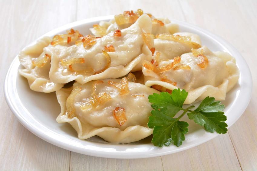 Pierogi ułożone na białym talerzu, posypane smażoną cebulką, udekorowane natką pietruszki.