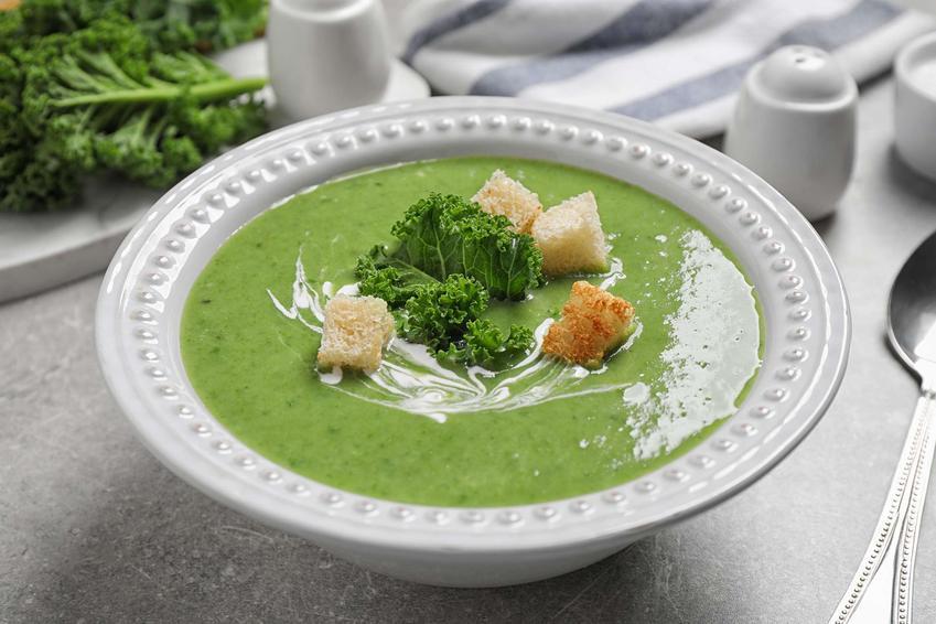 Zupa z jarmużu podana w głębokim, białym talerzu. Zupa ozdobiona jest śmietanką, kawałkiem liścia jarmużu i grzankami. Obok talerza, na szarym blacie, leży łyżka. W tle znajdują się menaże z przyprawami, ściereczka oraz liście jarmużu.