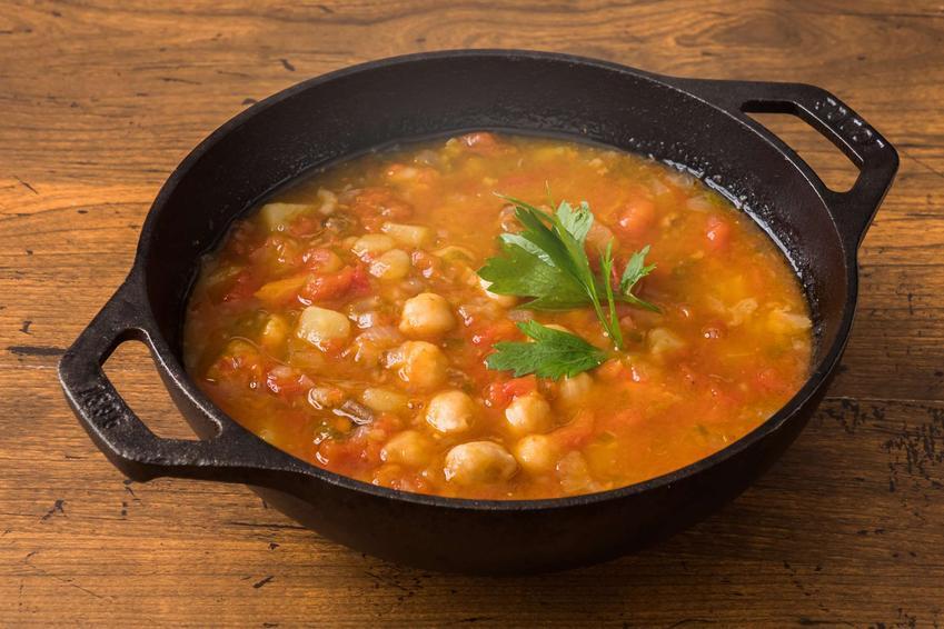 Zupa z ciecierzycy znajduje się w ciemnej misce, kształtem przypominającej żeliwny garnek. Miska ta stoi na drewnianym blacie.