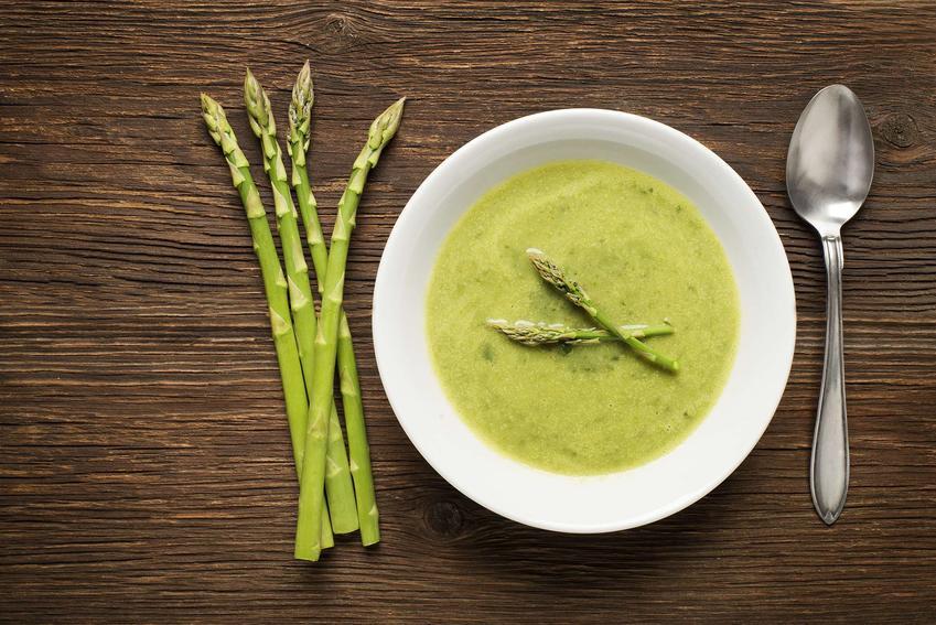 Zupa szparagowa znajduje się w białej miseczce. Obok niej leży metalowa łyżka oraz cztery szparagi zielone. Całość znajduje się na brązowym, drewnianym blacie.