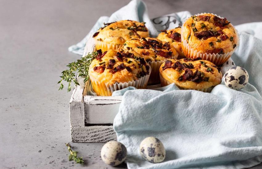 Muffinki pizzowe podane w jasnej, drewnianej skrzynce z jasną ściereczką, na szarym blacie