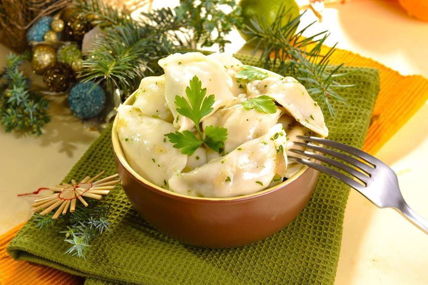 Pierogi wigilijne z kapustą i grzybami, ułożone w misce, udekorowane natką pietruszki.