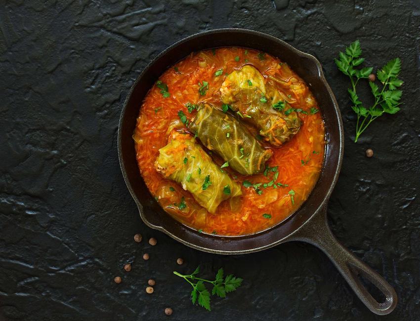Gołąbki z młodej kapusty podane w patelni żeliwnej w sosie pomidorowym na ciemnym blacie