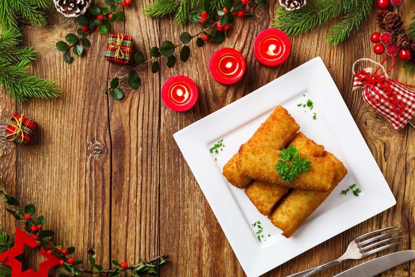 Krokiety na wigilię znajdują się na kwadratowym talerzu. Dookoła porozkładane są świąteczne ozdoby m.in. czerwone świeczki, maleńkie prezenty.