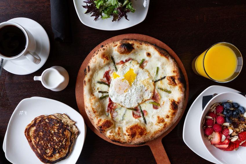 Pizza ze szparagami podana na drewnianej desce z innymi daniami, na brązowym stole
