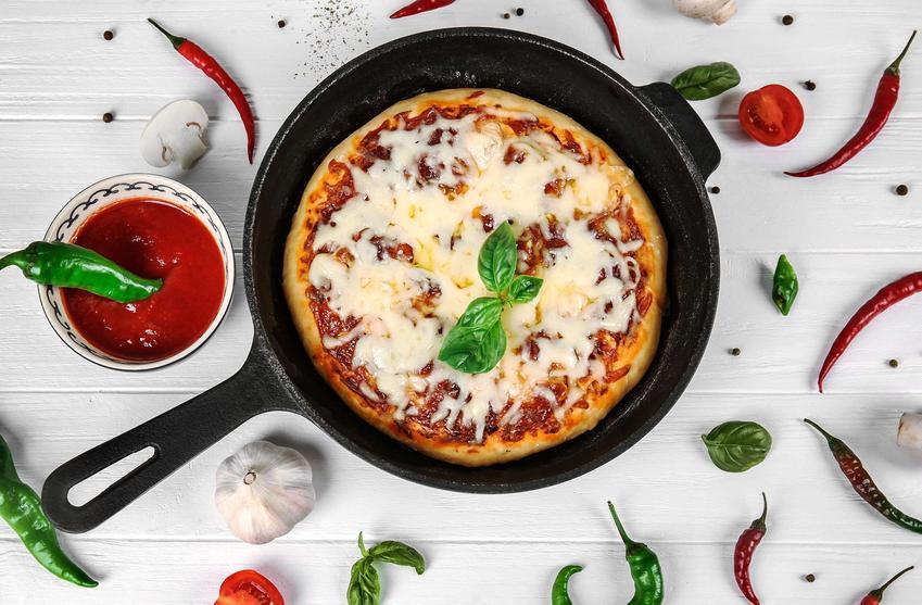 Pizza z patelni podana na patelni żeliwnej, z sosem pomidorowym, bazylią i papryczkami chili.