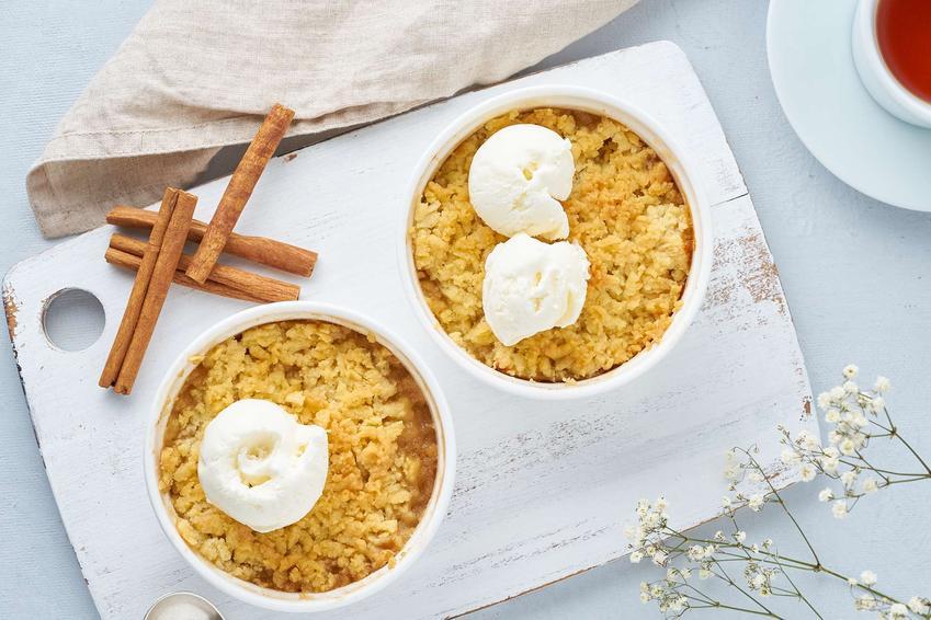 Ciasto z jabłkami i budyniem podane w dwóch kokilkach z lodami na białej desce, z laskami cynamonu, ściereczka, filiżanka a herbatą