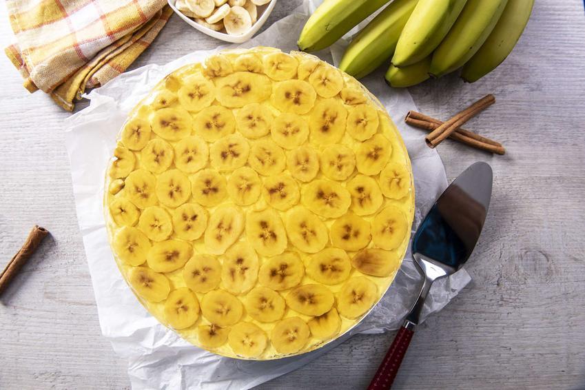 Bananowiec ciasto w okrągłej formie, na białej ściereczce, z łopatką do ciasta, laskami wanilii, bananami i biało-żółtą ściereczką