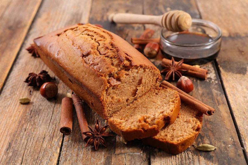 Ciasto piernikowe na drewnianym stole ozdobione laskami cynamonu, gwiazdkami anyżu, kardamonem, obok miseczka z miodem i nabierakiem do miodu.