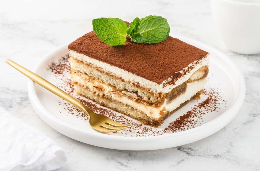 Ciasto tiramisu podane na białym talerzu ze złotym widelcem na białym, marmurowym blacie.