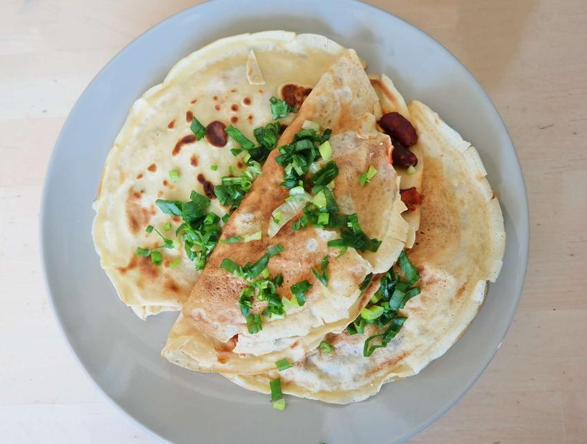 Naleśniki po meksykańsku z kurczakiem podane na białym talerzu, posypane cebulką dymką