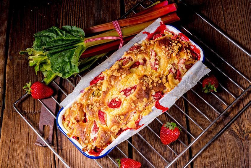 Ciasto z rabarbarem i truskawkami podane w prostokątnej foremce na kratce, z pęczkiem rabarbaru i truskawkami na drewnianym stole