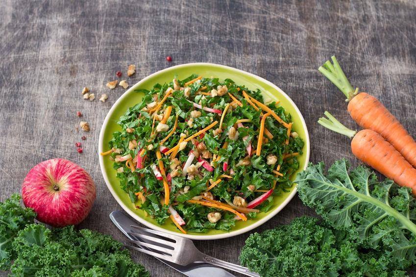 Zielony talerz z sałatką z jarmużem. Obok leżą liście jarmużu, jabłko, marchewka i pokuszone orzechy.