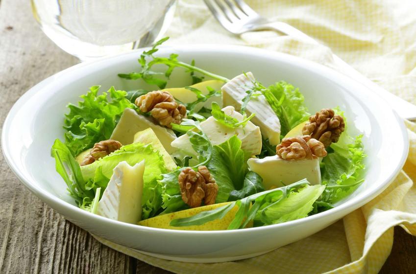Sałatka z gruszką podana w białej miseczce, na biało-żółtej ściereczce, obok widelec, szklanka z wodą, na drewnianym stole.