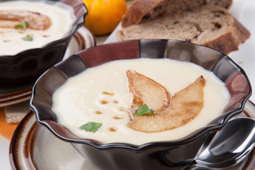 Z ciemnej dekoracyjnej miseczce znajduje się zupa z gruszki i pietruszki w formie kremu. Przyozdobiona jest kawałkami gruszki. W oddali widoczne jest pieczywo.