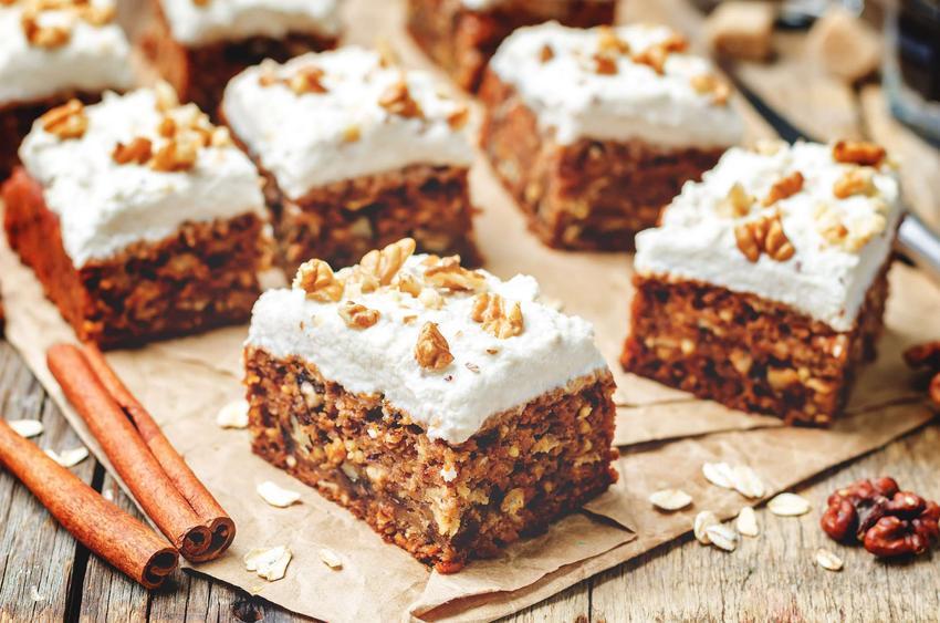 Ciasto wegańskie pokrojone w kawałki podane na papierze do pieczenia, z orzechami, laskami cynamonu i płatkami