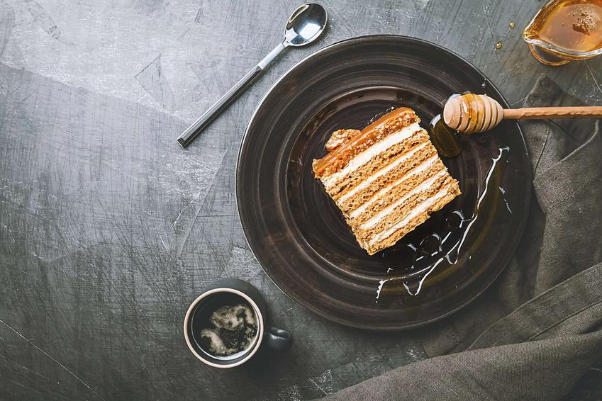 Ciasto miodownik podane na czarnym talerzu z dodatkiem miodu, obok nabierak do miodu, filiżanka, łyżeczka, na szarym blacie