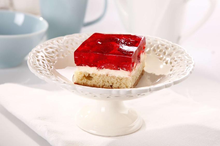 Ciasto z truskawkami i galaretką podane na białej paterze, na białym blacie, w tle miseczka i kubek błękitne