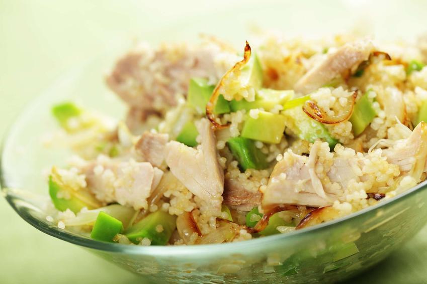 Sałatka z kuskus i kurczakiem podana jest w przezroczystej, szklanej salaterce.