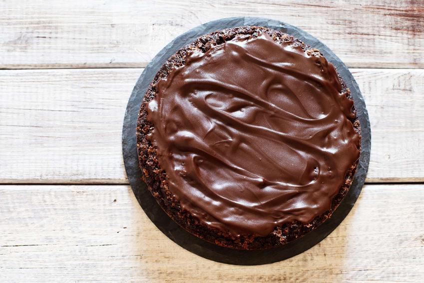 Ciasto urodzinowe podane na paterze znajdującej się na drewnianym blacie.