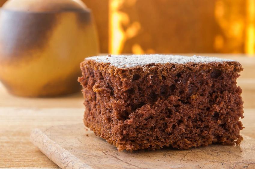 Ciasto kakaowe podane na drewnianej desce. Całość znajduje się na drewnianym stole.