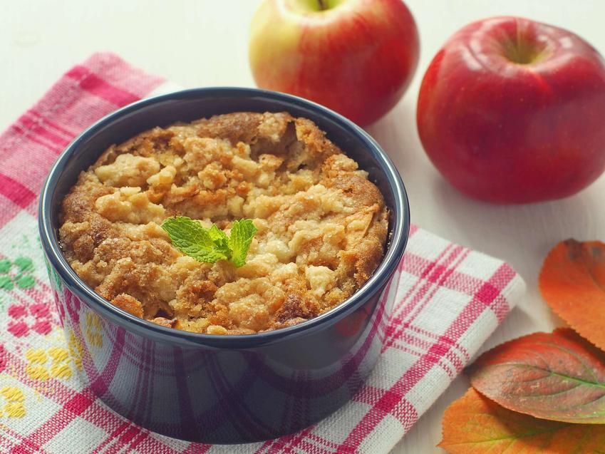 Ciasto drożdżowe z jabłkami znajduje się w wysokiej blaszce. Na stole poza nim leży kilka świeżych, czerwonych jabłek.