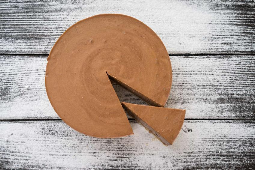 Sernik czekoladowy znajduje się na drewnianym blacie.