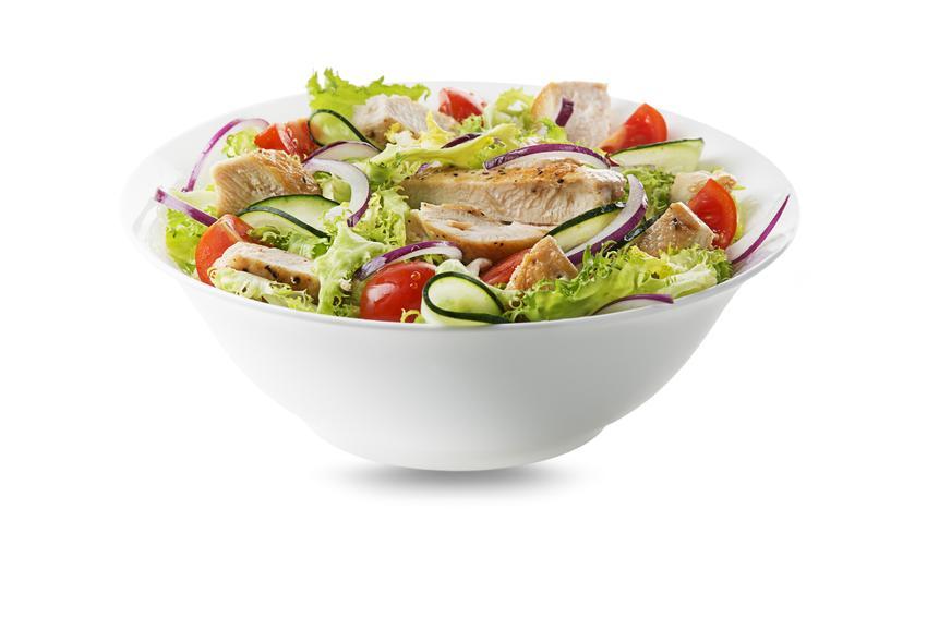 Sałatka z kurczakiem i sałatą lodową podana jest w białej, głębokiej miseczce.