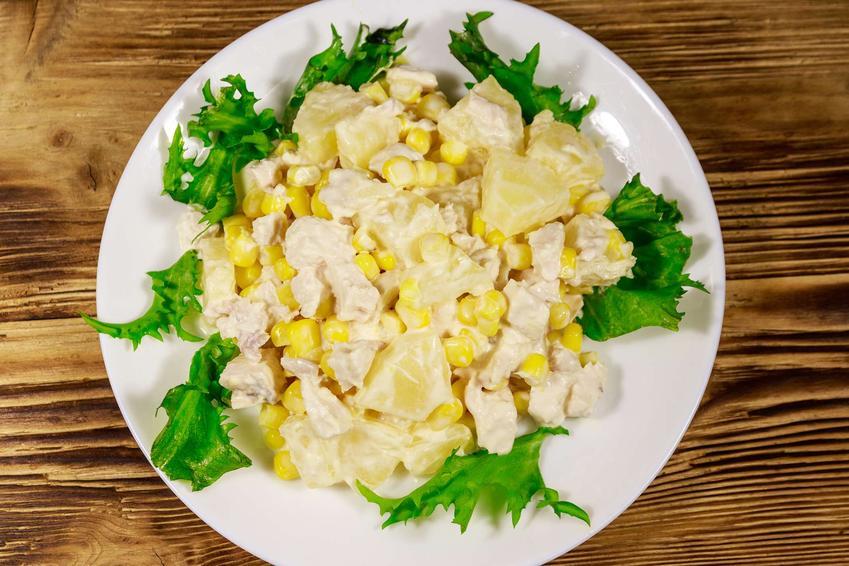 Sałatka z wędzonym kurczakiem i ananasem podana jest na białym talerzu, który znajduje się na drewnianym talerzu.